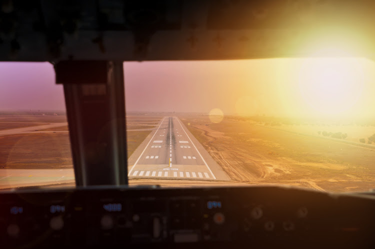 Final approach during sunset. View from flight deck of a modern airliner plane